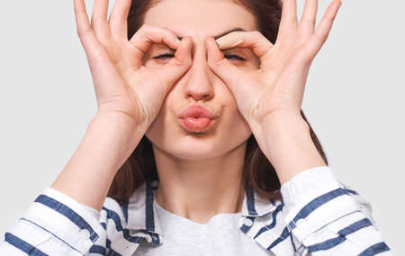Closeup portrait of funny young woman, showing Ok gestures with both hands, pretending to wear spectacles ot binocular and blowing air kiss. Pretty female student making grimace. Stock Photo
