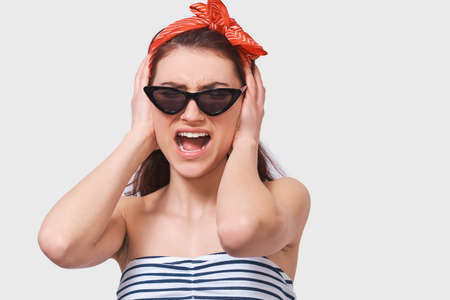 Screaming young student lady frowning her face feeling mad. People and emotions concept Stock Photo