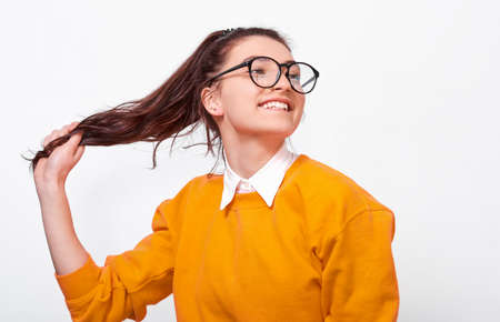Joyful teenager girl, smiling broadly, touching ponytail, wearing orange sweater and round transparent spectacles. Pretty female student posing over white studio wall. People and emotions Stock Photo