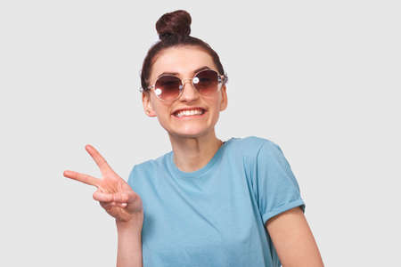 Portrait of happy beautiful girl with toothy smile, wearing blue t-shirt and round sunglasses, posing white studio background. Young student lady standing over grey wall and making peace gesture. Stock Photo