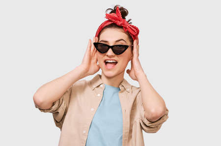 Amazed beautiful young lady wearing casualand trendy outfit, black sunglasses with red headband with mouth opened posing over white studio background. Surprised student girl holds head by hands. Stock Photo