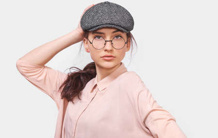 Beautiful young woman wears transparent round spectacles, casual pink shirt and gray cap, looks seriously directly into camera, poses in studio. People emotions concept