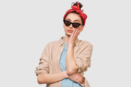 Pensive brunette young woman wears casual outfit and black sunglasses, ooks seriously directly into camera, poses against white studio background. People emotions concept Stock Photo