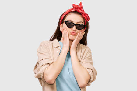 Cute teenager girl blowng air kiss, wears casual outfit and trendy black sunglasses. Positive student feels joyful posing over white studio wall. People and emotions Stock Photo