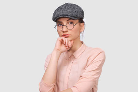 Portrait of serious brunette young woman wears transparent spectacles, casual shirt and gray cap, looks seriously directly into the camera, poses against white studio background. People emotions concept