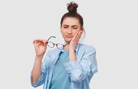 Questioned pretty young woman has thinking expression, looking through her transparent eyeglasses. Doubtful girl wears eyewear can`t make choice, has questioned expression, on white wall