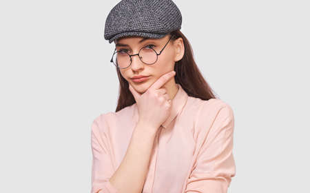 Closeup portrait of pensive young woman wears transparent round spectacles, casual shirt and gray cap, looks seriously to the camera, poses against white studio background. People and emotions concept