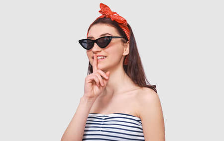 Studio portrait of Caucasian pretty young woman wears black sunglasses, red headband, holding index finger on lips, asking to keep silence. Mysterious female asks to be quiet.