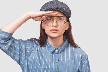 Closeup studio portrait of Caucasian young woman posing for advertisement wearing blue shirt, gray cap and round transparent eyeglasses, looking away with hand on forehead. Portrait of student girl.