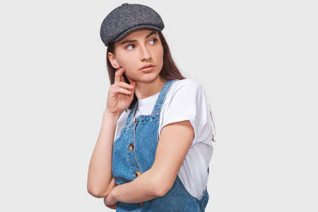 Image of questioned young woman, looking serious at discussing important things, dressed in casual trendy outfit, posing over white wall. Student girl has confused expression. People emotions