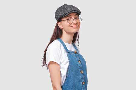 Puzzled young woman, looking through transparent eyewear directly to the camera, dressed in casual trendy outfit, posing over white wall. Student girl has confused expression. People emotions