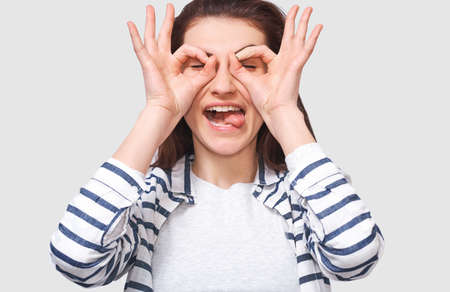 Closeup horizontal studio image of cheerful and funny young woman, showing Ok gestures with both hands, pretending to wear spectacles ot binocular. Pretty female showing tongue.
