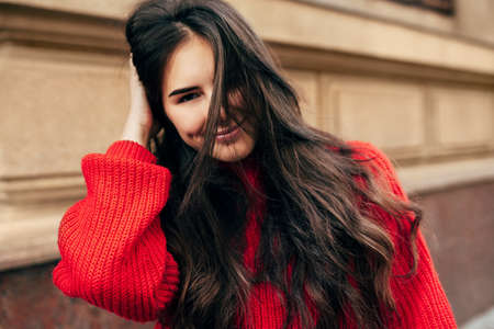 Smiling European brunette woman with long hair looking directly to the camera. Outdoor portrait of blissful female model in trendy knitted red sweater posing during walking in the city street. Stock Photo