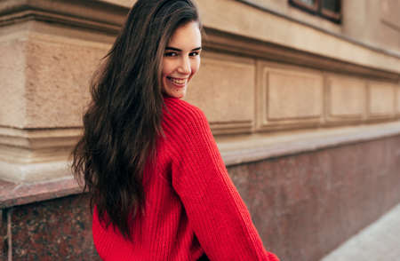 Outdoor rear view portrait of beautiful young brunette woman smiling, follow me on the city street. Pretty female model in trendy knitted red sweater walking in the town. Travel, people, lifestyle