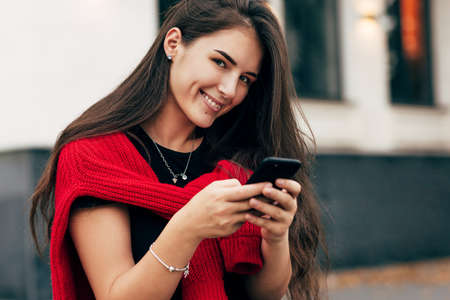 Portrait of smiling positive young woman sitting outdoors texting on mobile phone. Brunette female wears red sweater and black t-shirt resting outside in the city street browsing on her smart phone. Stock Photo