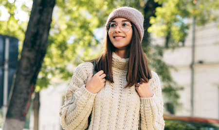 Outdoor image of smiling student female looking aside, walking on the street in the morning, wearing knitted sweater, eyeglasses and hat. Beautiful young woman with backpack posing outside Stock Photo