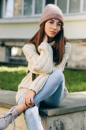 Attractive student female looking at the camera, sitting on the bench in the city street, wearing knitted sweater, eyeglasses and hat. Beautiful young woman with backpack posing outside