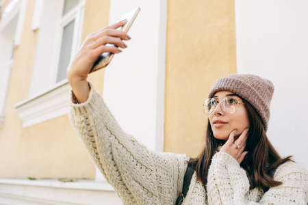 Beautiful young woman standing outdoors against building's wall and taking self portrait on smart phone. Brunette female dressed in knitted sweater, hat, eyeglasses making selfie on the city street.