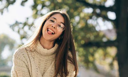 Close-up outdoor portrait of funny student woman showing tongue out, looking to the camera, wearing knitted sweater and transparent eyeglasses. Beautiful happy young female posing outside on sunlight