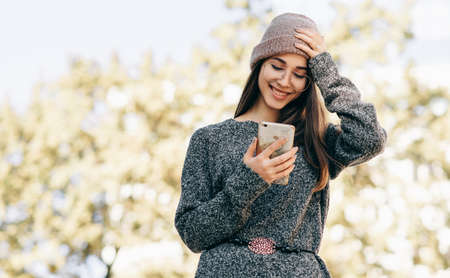 Image of smiling young woman standing outdoors chatting with her friend on smart phone. Brunette female dressed in knitted sweater, hat, eyeglasses browsing online on the city street.