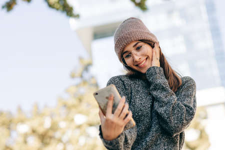 Outdoor portrait of beautiful young woman standing against building's wall and taking self portrait on smart phone. Female wears knitted sweater, hat, eyeglasses making selfie on the city street.