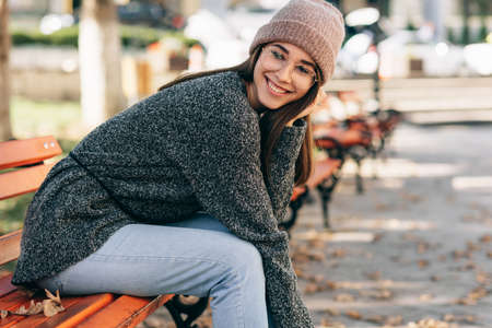 Image of pretty smiling student female looking to the camera, sitting on the bench in the city street, wearing knitted sweater, eyeglasses and hat. Beautiful young woman resting outside