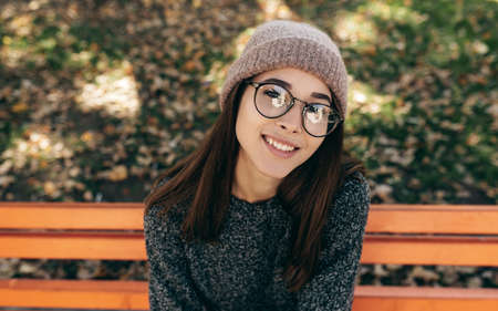 Top view close-up portrait of beautiful young brunette woman smiling broadly, wearing eyeglasses, knitted sweater and hat. Outdoor portrait of pretty female model posing during walking in the street.