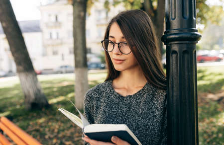 Pretty young woman wearing sweater and transparent eyeglasses, standing outdoor on the city street and reading the book while waiting her friends. Young female student learning in the city street.