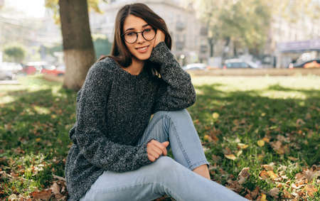 Horizontal outdoor image of pretty smiling student female looking to the camera, sitting on green grass in the city park, wearing knitted sweater and eyeglasses. Beautiful young woman resting outside