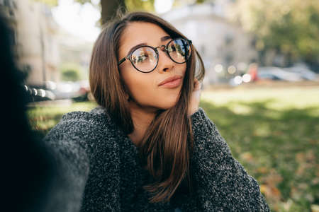 Close-up portrait of beautiful young woman relaxing outdoor and taking self portrait on smart phone. Female wears knitted sweater, transparent eyeglasses making selfie on the city street. Stock Photo
