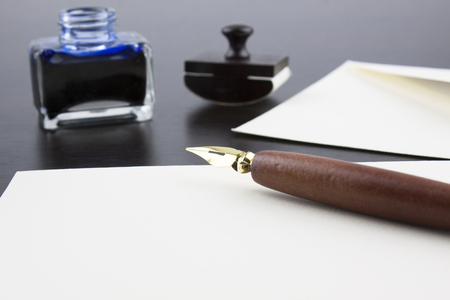 ink pot: Pens, ink pot, papyrus and blotting paper on a brown table