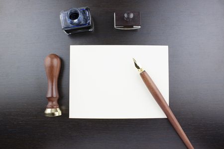 papyrus: Pens, ink pot, papyrus and blotting paper on a brown table