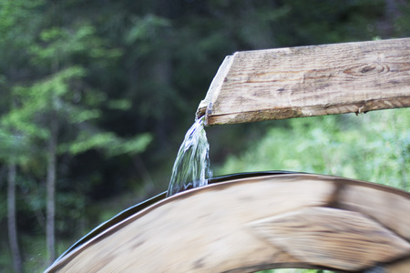 water mill: Water flowing from a trough on a water mill wheel