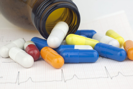 electrocardiograma: Pills pouring form a glass container on a EKG heart sheet