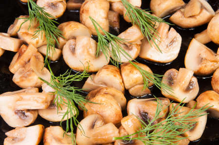quartered: Quartered Roasted Champignons With Dill On A Black Frying Pan
