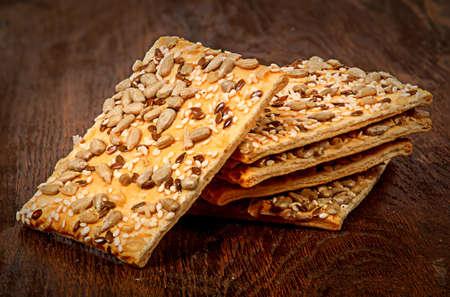 galletas integrales: Pila de galletas de cereal con las semillas en una mesa de madera
