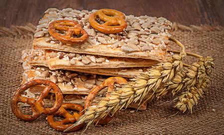 galletas integrales: galletas Pila de cereales con semillas y espigas de trigo en el despido y la mesa de madera