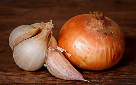 Closeup of onion and garlic on wooden table