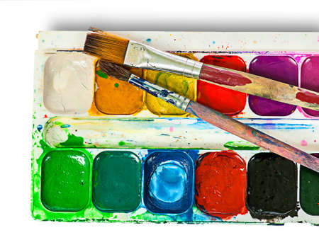 Closeup of watercolor paints set and brushes isolated on white background