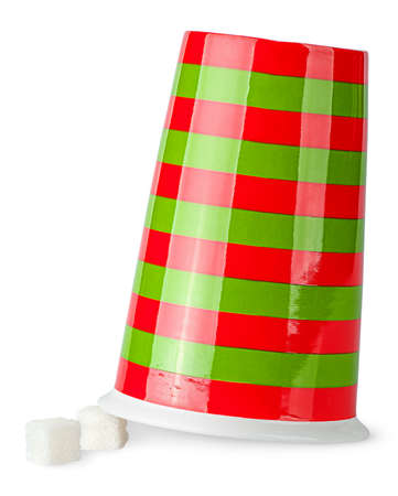 epicure: Inverted red and green cup with sugar cubes isolated on white background