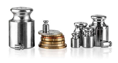 scaling: Several old scaling weights and coins isolated on white background