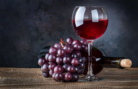 Glass wine with grapes and bottle