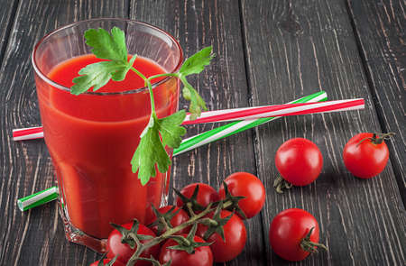 Glass of tomato juice on wooden table