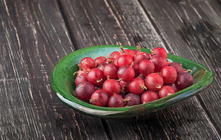 Red gooseberry in clay bowl 写真素材