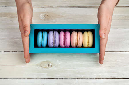 Female hands holding box with macaroons on wooden background