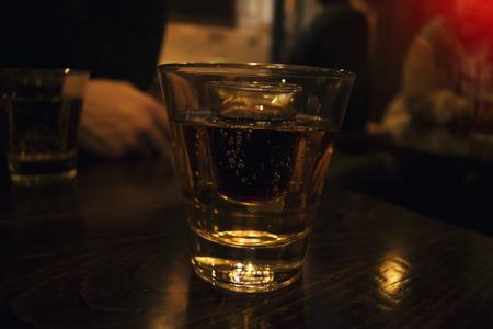 Een glas sterke alcohol binnen een glas energizer, twee glascocktail, bij weinig licht binnen een barachtergrond Stockfoto