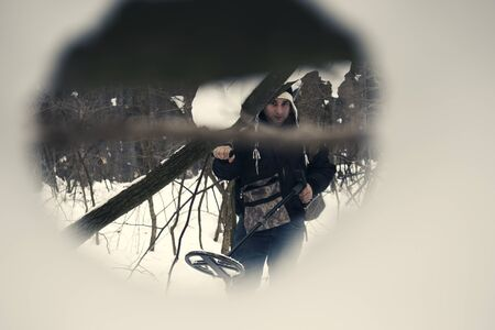 Young man metal detecting in snow holding metal detector