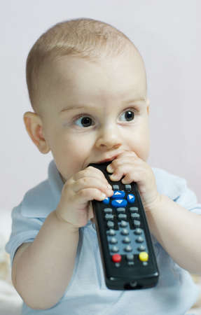 tv remote: Curious baby girl chewing tv remote control