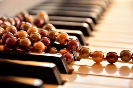 fortepian: Pearl naszyjnik na klawiaturze fortepianu Zdjęcie Seryjne