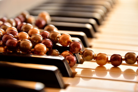 masterly: Pearl necklace on piano keyboard Stock Photo